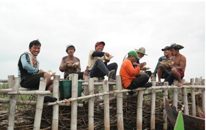 Anggota Kelompok Tani Sringin Trimulyo beristirahat saat penanaman mangrove